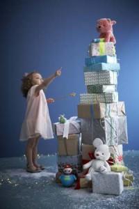 Mädchen an Weihnachten vor einem Geschenkebeg