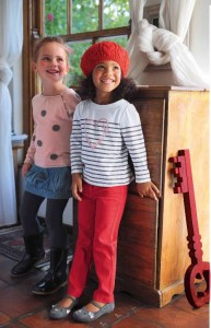 zwei kleine Mädchen lehnen an einer Kommode
