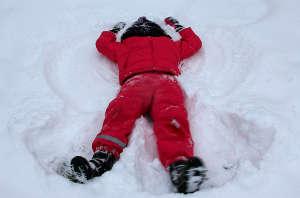 ein Kind spielt im Schnee und macht einen Schneeengel