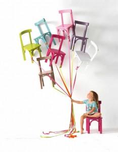 Mädchen mit vielen bunten Stühlen