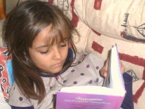 Ein Mädchen liest ein Buch in der Bibliothek