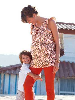 ein kleiner Junge umschlingt fröhlich das Bein seiner Mutter