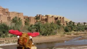 Maskottchen Palle vor einer Stadt in Marokko