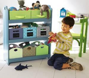 Spielender Junge vor einem Regal mit Spielzeug