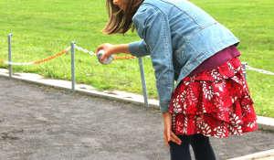 Mädchen im Vertbaudet-Outfit beim Boule-Tournier