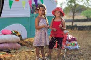 Zwei Mädchen vor einem Campingwagen