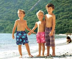 Drei Jungen in Badehosen vor dem See