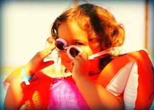Mädchen mit Sonnenbrille und Schwimmflügeln am Strand