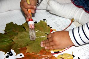Kind bestreicht ein Blatt Laub mit Kleber