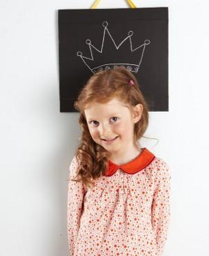Schülerin vor einer Tafel mit Kreide-Krone