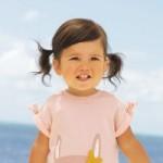 Kleines Mädchen mit Zöpfen vor dem Meer