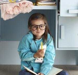 Verschmitzt lächelndes Mädchen mit Malbuch