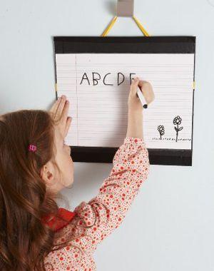 Mädchen übt an der Tafel das ABC
