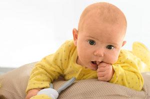 Baby im gelben Strampler lutscht auf Daumen