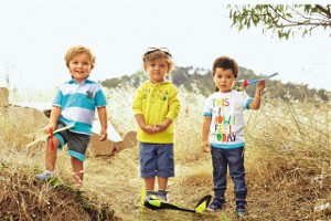 3 Jungen spielen draußen mit Flugzeugen