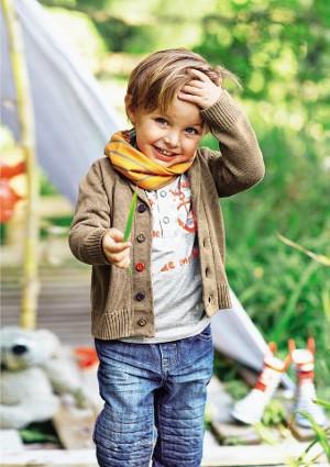 Verschmitzt lächelnder Junge vor einem Zelt