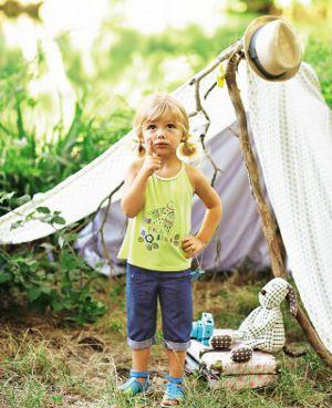 Mädchen steht grübelnd vor einem Zelt