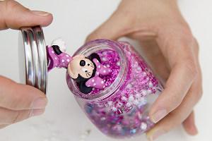 Deckel mit Minnie Maus-Figur wird auf ein Glitzerglas gesetzt
