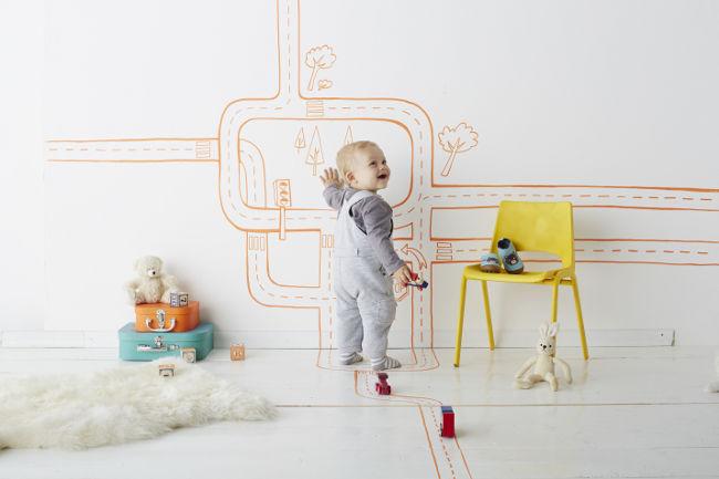 Lachender kleiner Junge vor bemalter Kinderzimmerwand