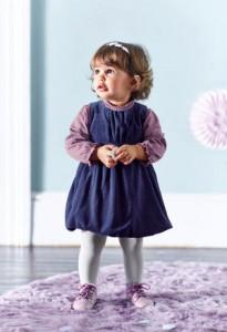 Kleines Mädchen im Kleid guckt drollig
