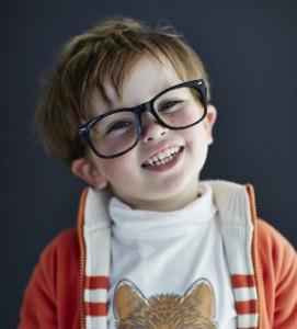 kleiner, fröhlicher Junge mit großer Brille
