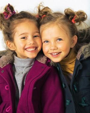 2 Mädchen in Jacken freuen sich auf  den Waldausflug