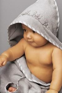 Baby im Bademantel nach dem Babyschwimmen
