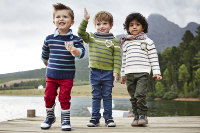 3 Jungen in Herbstkleidung auf einem Anlegesteg vorm See