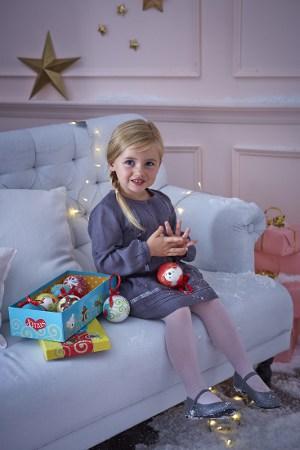 Mädchen mit Weihnachtskugeln auf dem Sofa