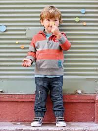 Kleiner Junge tippt sich mit dem Finger gegen die Nase