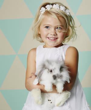 Mädchen im weißen Kleid mit Kaninchen