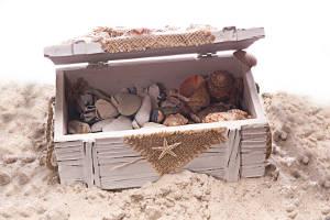 Schatzkiste mit Muscheln und Steinen im Sand