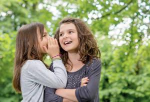 2 Mädchen flüstern sich im Garten etwas zu