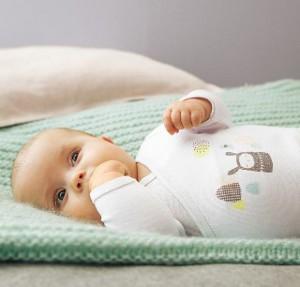 liegendes Baby mit Hand vor dem Mund