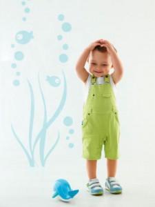 Kleiner Junge im Overall mit Wasser-Deko