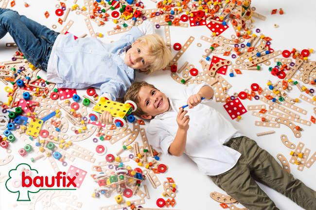 2 Kinder spielen mit vielen Baufix-Teilen