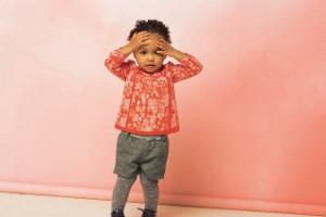 Kleines Mädchen schlägt die Hände über den Kopf