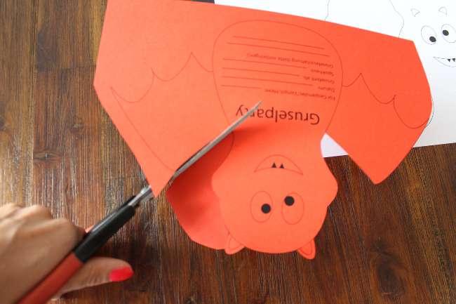 Fledermaus auf rotem Papier wird ausgeschnitten