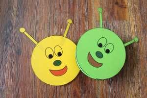2 gebastelte Raupen mit fröhlichen Gesichtern