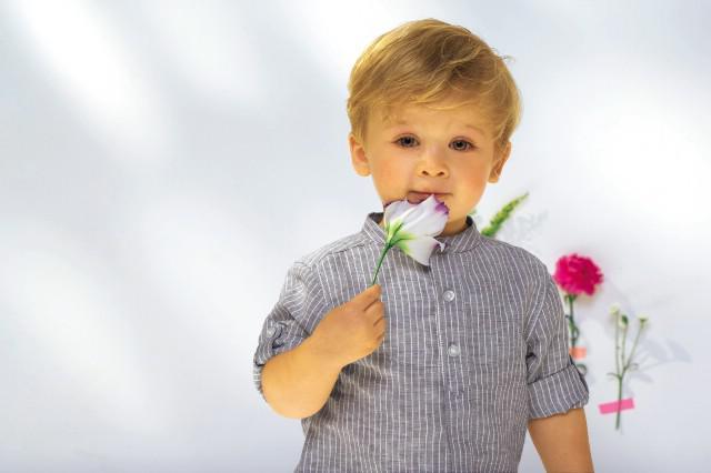 ein kleiner Junge riecht an einer Blume