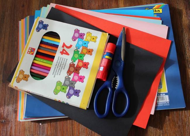 farbiges Tonpapier, Schere, Klebestift und Stifte zum Basteln