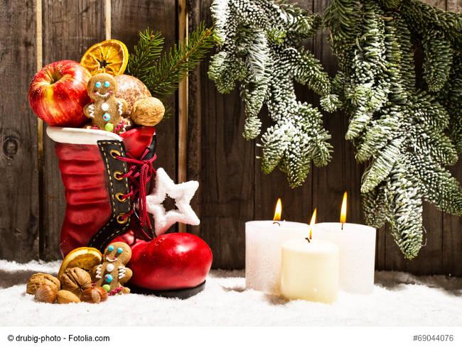 Gefüllter Nikolausstiefel, brennende Kerzen, Tannenzweige und Schnee