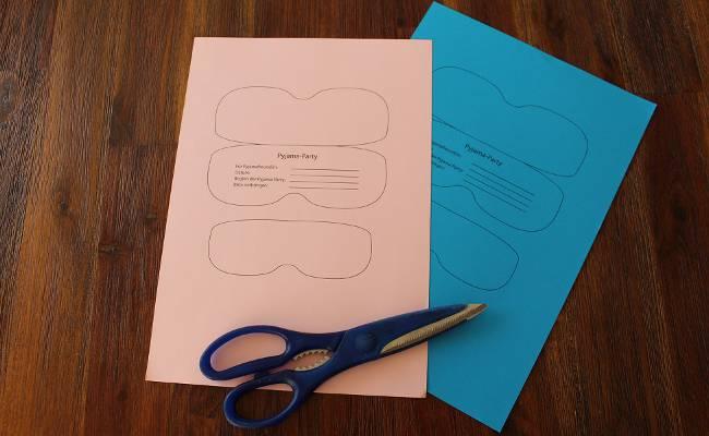 farbiges Tonpapier mit Schlafmasken-Einladung zum Ausschneiden
