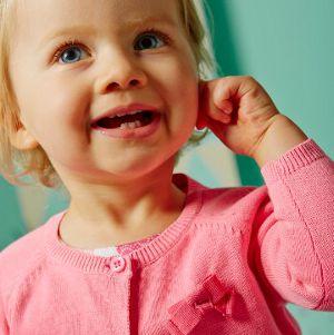 kleines Mädchen fasst an ihr Ohr