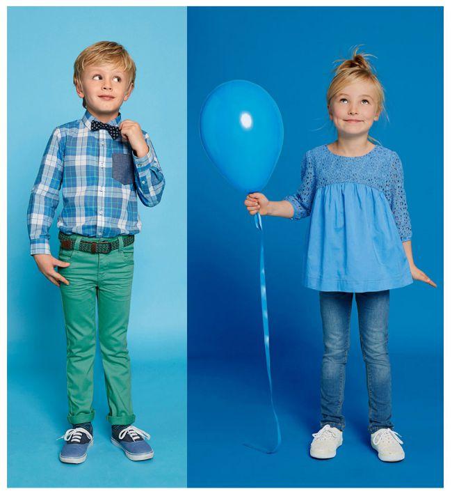 Junge und Mädchen in blauen Outfits vor blauem Hintergrund