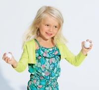 Kleines Mädchen hält zwei kleine Bälle in den Händen