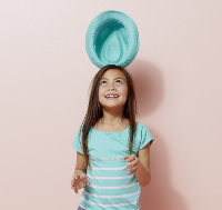 Kleines Mädchen balanciert einen Hut auf dem Kopf