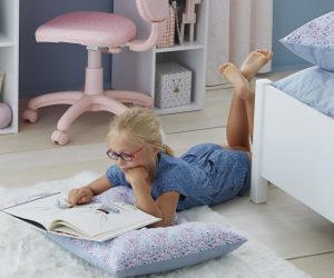 Mädchen liegt lesend auf dem Fußboden