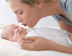 junge Mutter liebkost ihr schlafendes Baby