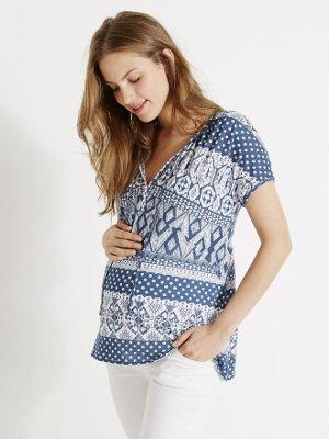 eine schwangere Frau legt die Hand auf ihren noch flachen Bauch